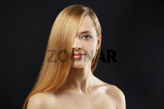 Attractive girl with straight hair on a dark background