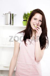 junge frau isst ein stück gurke