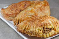 pasties filled with minced meat on a white plate w