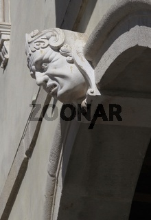 Head with strong facial expression, architectural detail of a Renaissance facade in Italy.