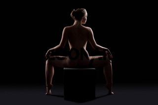 Beautiful nude woman posing on cube silhouette