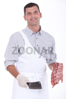 a butcher taking a chopper and pork ribs