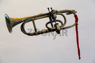 Antique bugle or trumpet isolated against grey