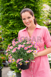 Smiling woman hold pink potted flower