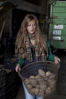 junge Frau trägt Korb mit Kartoffeln