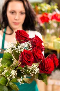 Young woman making flower bouquet florist shop