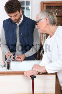 young man fixing faucet for older woman