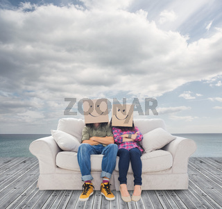Couple sitting on couch with cardboard over their head