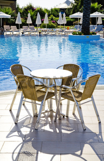 table and chairs near a cool pool in a hot canicular day
