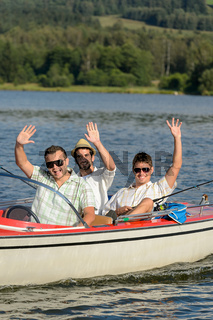 Cheerful young men sitting in motorboat