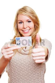 Frau mit Führerschein hält Daumen hoch