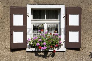 Fenster mit bunten Fensterläden und Geranien im Blumenkasten