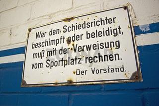 Wer den Schiedsrichter beschimpft oder beleidigt, muß mit der Verweisung vom Sportplatz rechnen, Schild am Eingang eines Sportpatzes