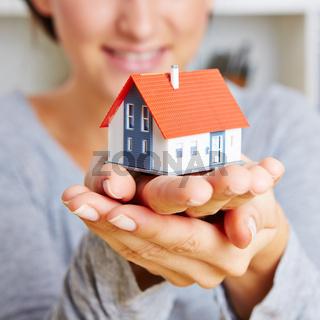 Hände halten ein kleines Haus