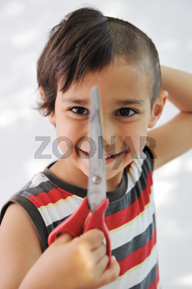 Kid cutting hair to himself with scissors, funny look