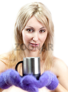 Portrait of the young blonde woman in fluffy mittens with a mug