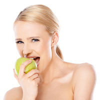 Side view of blond woman she bites an apple