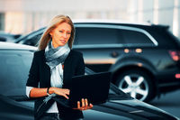Young businesswoman with laptop on the car parking