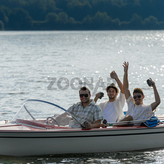 Cheerful young men drink beer speed boat