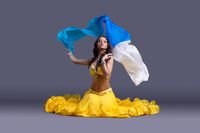 Pretty dancer in yellow costume sitting on floor