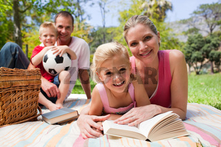 Mother and her daughter reading lying on a picnic tablecloth