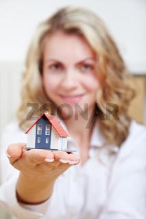 Frau hält Haus auf Hand