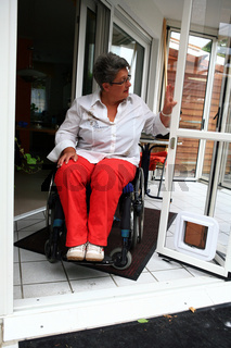 Frau im Rollstuhl in ihrer barrierefreien Wohnung