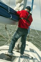 man holds the mainsail of a sailing yacht
