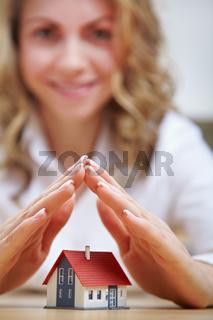 Frau hält Hände über Haus