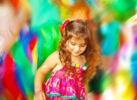 Adorable small girl dancing over blur colors background