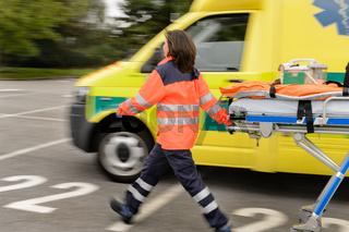 Blurry paramedics pulling gurney ambulance car