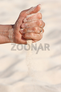 Sand running through hands n beach
