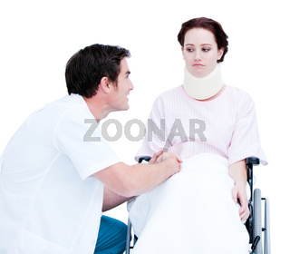 Attentive male doctor discussing with a patient in a wheelchair against a white background