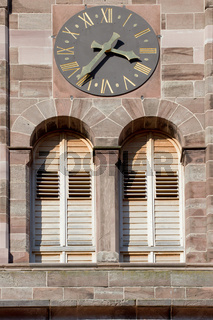 Ausschnitt eines Kirchturms mit zwei Fenstern und einer großen Uhr