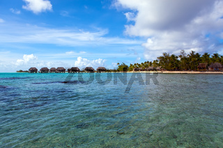 View on tropical island and small houses on the sea. Polynesia