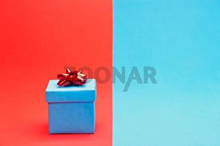 Ein blaues Geschenk vor einem blau-rotem Hintergrund