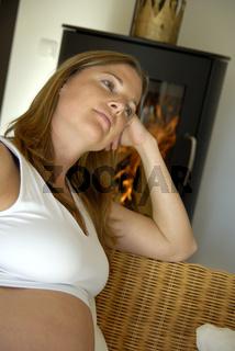 Schwangere Frau sitzt vor einem Holzofen