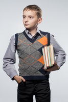 Little boy with books in hands. Looks aside.