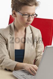 Angestellte schreibt am Laptop