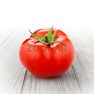 red tomato isolated on wood