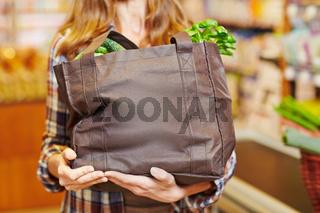 Frau trägt volle Einkaufstasche mit Gemüse