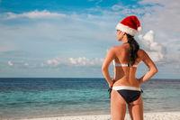 Woman in santa hat on the beach
