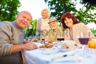 Glückliche Senioren am gedeckten Kaffeetisch