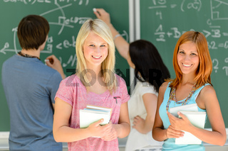 Two smiling student girls in math class