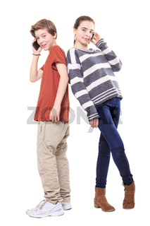 two smiling teenager, back on back with their mobile phones, isolated on white