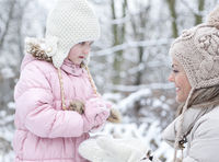 Mutter und Tochter formen Schneeball im Winter