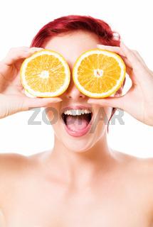 begeisterte junge frau hält orangen vor die augen