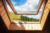 Open window at village wooden house in mountains. Amazing view of summer landscape with forest and meadow under blue sky