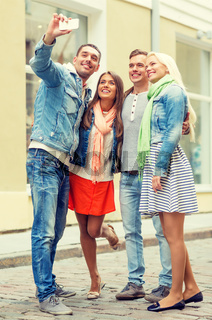 group of smiling friends making selfie outdoors