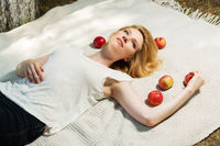Happy young woman with apples lying on the cover